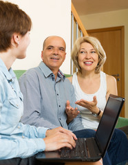 Happy eldelry couple talking with employee with laptop