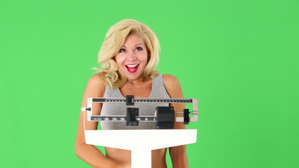 Happy young woman weighing self on scales