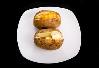 Two Baked Potatoes with Butter and Cheese