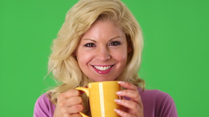 Portrait of young blond woman drinking from a cup