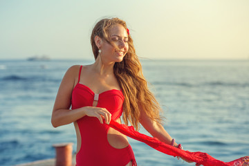 Girl at the sea in a red bathing suit