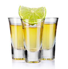 Three gold tequila shots with lime isolated on white