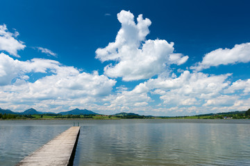 wooden boardwalk at lake hopfen am see with blue sky and clouds
