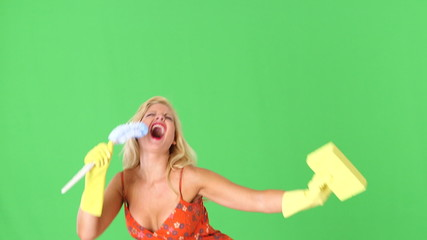 Sexy blonde woman with toilet bowl brush and sponge, singing