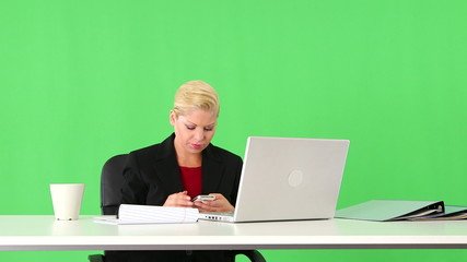 Executive businesswoman working with cellphone and laptop at des
