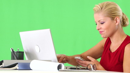 Businesswoman working with cellphone and laptop at desk