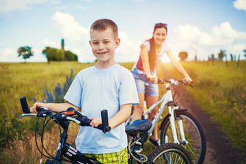 Happy family. mother and son riding bicycle in the field