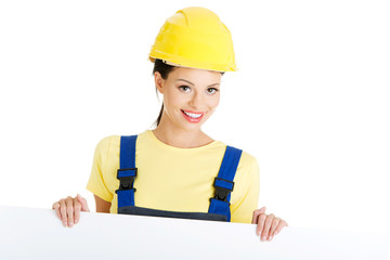 Construction worker woman holding blank board.