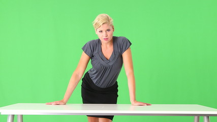 Portrait of businesswoman leaning on desk