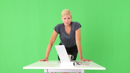 Portrait of businesswoman leaning on desk with cup of coffee