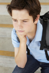 Unhappy Pre teen boy at school