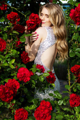Fashion beauty girl with red roses flowers