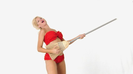 Sexy blond girl in red bikini playing guitar on broomstick and d