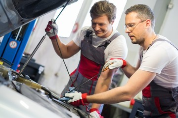 Two mechanics checking oil level in a car workshop
