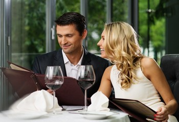 Cheerful couple with menu in a restaurant