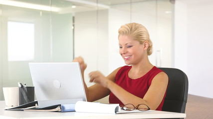 Positive businesswoman at desk with laptop showing excitement wh
