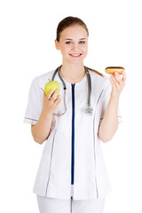 Dietician holding doughnut and fresh apple.