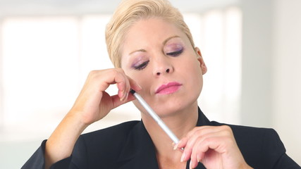 Closeup of executive businesswoman thinking with pen in hand
