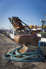 fishing boats in harbor - bollard with blue rope