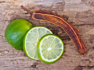 Green limes and tamarind on wooden background.