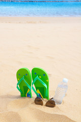 green sandals on sandy beach