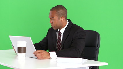 Male executive at desk with laptop and cell phone
