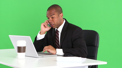 Male executive at desk with laptop and talking on cell phone