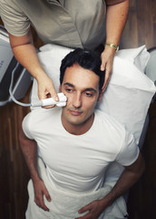 Handsome man having facial laser rejuvenation procedure