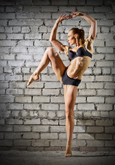 Muscular dancing woman on brick wall (normal version)