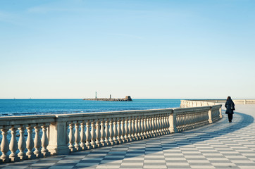 Solitary woman walking on Mascagni terrace in front of the sea,