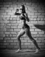 Muscular woman on grey brick wall (monochrome version)