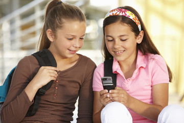 Pre teen girls in school with cellphone