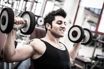 Young man exercising with dumbbells in a gym. Filtered image.