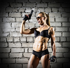 Muscular woman with gun on brick wall (dark version)