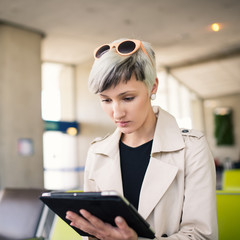 Businesswoman working with tablet at Charles de Gaulle airport,