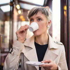 Young woman drinking coffee in a cafe in Paris, France. Shallow