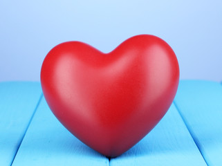 Decorative red heart on blue wooden table on blue background