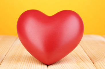 Decorative red heart on wooden table on orange background