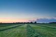 summer sunrise over fresh hay on pasture