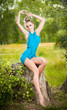 beautiful blonde woman wearing blue dress posing on a stump