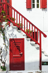 Close-up of traditional white house with red railing, door and s