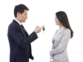 man handing car key to woman
