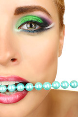 Beautiful woman with bright make-up and necklace in mouth,