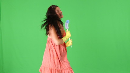 Cute young woman dancing with toilet brush and sponge