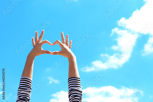 canvas print picture Young girl holding hands in heart shape framing