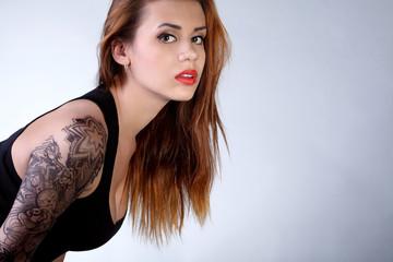 Молодая девушка с татуировкой на руке