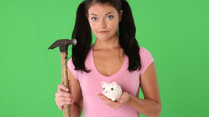 Closeup portrait of young woman holding a piggy bank and hammer