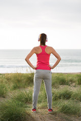 Fitness female athlete standing towards the sea