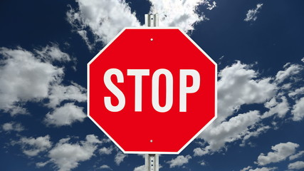 Stop Sign with Time Lapse Clouds