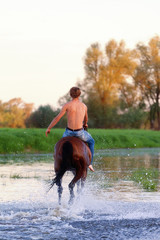 rider with a naked torso skips astride a horse down the river